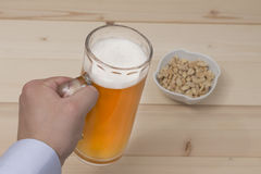 Male hand holding a mug of draft beer. Peanuts in the bowl on the table. Stock Photography