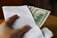 Male hand holding and passing a white envelope full of American Dollars (USD, US Dollars) as a symbol of illegal cash transfer, mo Royalty Free Stock Photos