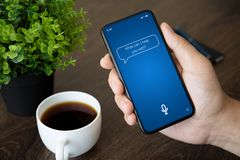 Male hand holding phone with app personal assistant on screen. Above the table in office royalty free stock image
