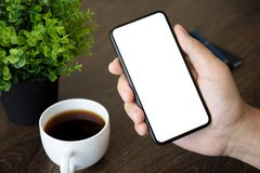 Male hand holding phone with  screen in the office. Male hand holding phone with  screen above the table in office royalty free stock photos