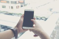 Male hand holding a phone on a shopping mall. Concept technology Royalty Free Stock Photography