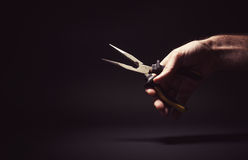 Male Hand Holding a Pliers. Conceptual composition, male hand holding a pliers Royalty Free Stock Image