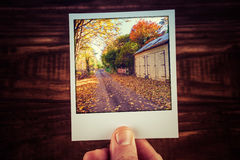 Male hand holding polaroid photo of rural road passing wooden sh Stock Images