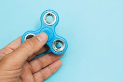 Male hand holding popular fidget spinner toy on the blue background stock photography