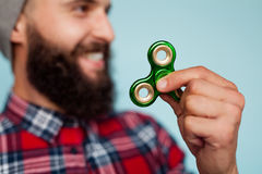 Male hand holding popular fidget spinner toy. Happy Male with beard smiling and holding popular fidget spinner toy over blue background royalty free stock photos