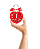 Male hand holding red clock mark at 7 o`clock mean wake up time Royalty Free Stock Images
