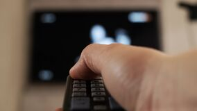 Male hand holding remote the control turn off smart tv. Close up.