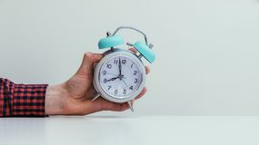 Retro styled white alarm clock in man's hand,. Male hand is holding a retro styled white alarm clock, time todo daylight saving riser morning wakeup pink stock photos
