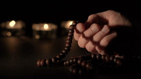 Male hand holding rosary beads. Hands holding rosary beads and over black background stock footage