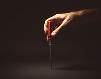 Male Hand Holding a Screwdriver. Conceptual composition, man's hand holding a screwdriver Royalty Free Stock Photography