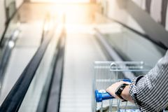 Male hand holding shopping cart on travelator. Male hand shopper holding shopping cart trolley on travelator escalator in supermarket or grocery store. Shopping Royalty Free Stock Photo