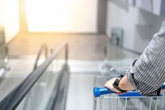 Male hand holding shopping cart on travelator. Male hand shopper holding shopping cart trolley on travelator escalator in supermarket or grocery store. Shopping Royalty Free Stock Photos