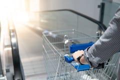 Male hand holding shopping cart on travelator. Male hand shopper holding shopping cart trolley on travelator escalator in supermarket or grocery store. Shopping Stock Image
