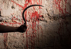 Male hand holding a sickle in front of blood stained wall Royalty Free Stock Image
