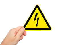 Male hand holding sign of danger voltage symbol Royalty Free Stock Images