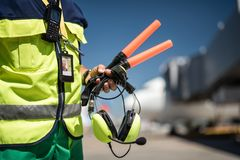 Male hand holding signal wands and headphones. Waiting for plane. Close up of airport worker torso in vest and arm with headset. Airdrome on blurred background Royalty Free Stock Photography
