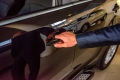 Business man hand holding car doorhandle Stock Photo