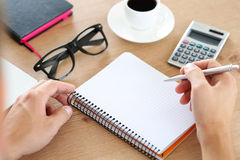 Male hand holding silver pen ready to make note in opened notebook. royalty free stock image