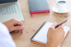 Male hand holding silver pen. Ready to make note in opened notebook. Businessman or employee at workplace writing business ideas, plans or tasks at personal Royalty Free Stock Photo