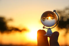 male hand holding small crystal globe in front of sunset royalty free stock photo