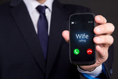 Male hand holding smart phone with incoming call from wife. Relationship concept - male hand holding smart phone with incoming call from wife royalty free stock photography