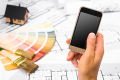 Male Hand holding a Smart Phone over Construction plans Stock Images