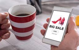 Big sale concept on a smartphone. Male hand holding a smartphone with big sale concept Stock Images