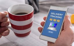 Delivery tracking concept on a smartphone. Male hand holding a smartphone with delivery tracking concept Royalty Free Stock Image