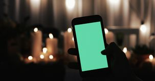 Male Hand is Holding Smartphone with Green Screen. Few types of motion - swipe right and tapping. Lighted candles in the stock video footage