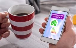 Home energy efficiency concept on a smartphone. Male hand holding a smartphone with home energy efficiency concept royalty free stock photos