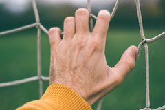 Male hand holding soccer net Stock Images