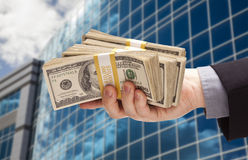 Male Hand Holding Stack of Cash with Corporate Building Stock Photography