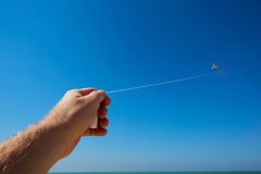 Male hand holding strings with a kite in sky Royalty Free Stock Photography