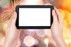 Male hand holding a tablet touch computer gadget. With touch blank screen on firework and bokeh lights background Stock Photos