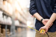 Male hand holding tape measure in warehouse. Close up of male hand holding yellow tape measure in warehouse. Furniture product design measuring concept Stock Images