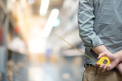 Male hand holding tape measure in warehouse. Close up of male worker hand holding yellow tape measure in warehouse. Furniture product design measuring concept Royalty Free Stock Images