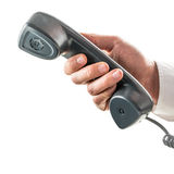 Male hand holding a telephone receiver Royalty Free Stock Photography