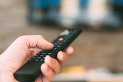 Male hand holding television remote controller