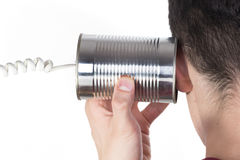 Male hand holding a tin can phone to his ear Royalty Free Stock Images