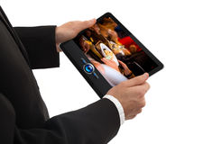 Male hand holding a touchpad pc showing a movie Stock Image