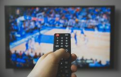 Basketball match. Male hand holding TV remote control. Basketball match royalty free stock images