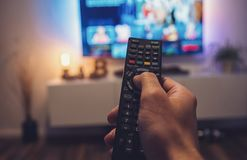 Male hand holding TV remote control. Point of view shot. POV-Shot from a mans hand holding a TV Remote control to ZAP on tv at home. ideal for websites and Royalty Free Stock Image