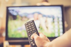 Male hand is holding TV remote control, streaming on a smart TV stock photos