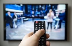 Talk show. Male hand holding TV remote control. Talk show stock image
