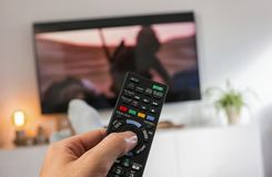 Male hand holding TV remote control and Watch tv. POV-Shot from feeds and a hand holding a TV Remote control to ZAP on tv at home. ideal for websites and Royalty Free Stock Images