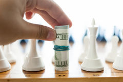 Male hand holding twisted banknotes and making move at chess Stock Images