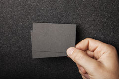 Male hand holding two black business cards on the stock photos