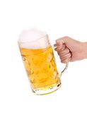 Male hand holding up a glass of beer. Stock Image