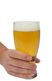 Male hand holding up a glass of beer over a white Royalty Free Stock Images