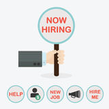 Male hand holding vertical circle paddle stick and word Now Hiring. With extra word HELP, word NEW JOB, word HIRE ME, dollar sign, and megaphone icons Stock Photo